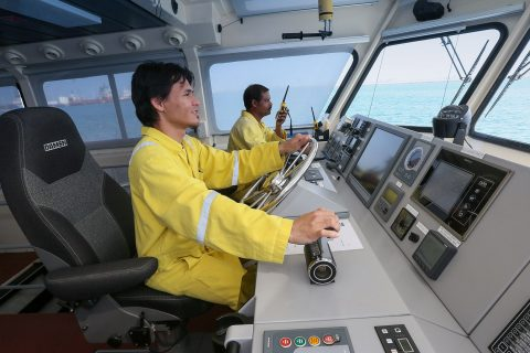 Tugboat captain communicating with local port authorities